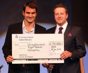 """Turnierdirektor Ralf Weber (rechts) übergibt Roger Roger Federer, GERRY WEBER OPEN-Finalist 2013, einen Scheck in Höhe von 40.000 Euro für seine Afrika-Stiftung, die """"Roger Federer Foundation"""". © GERRY WEBER OPEN (HalleWestfalen)"""