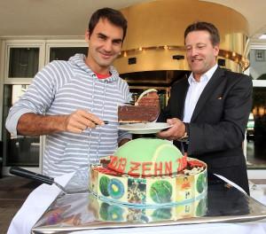 Vor zehn Jahren gewann Roger Federer erstmals die GERRY WEBER OPEN und anschließend Wimbledon. Daran erinnerte Turnierdirektor Ralf Weber den Rekord-Grand-Slam-Sieger bei seiner Ankunft in HalleWestfalen mit einer Jubiläumstorte, die dann beide gemeinsam vor dem GERRY WEBER Sportpark Hotel anschnitten. © GERRY WEBER OPEN (HalleWestfalen)