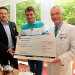 Tennis-Superstar Roger Federer (Mitte) und Turnierdirektor Ralf Weber (links) übergaben einen 5.000-Euro-Scheck an Professor Dr. Johannes Otte (Chefarzt Kinder- und Jugendklinik Bethel). © GERRY WEBER OPEN (HalleWestfalen)